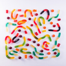 Pattern Of Colorful Gummy Bears And Worms Against White Background Top View.