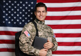 Cadet with backpack and tablet against American flag. Military education