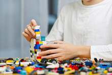 Close Up Of Child's Hands Playing With Colorful Plastic Bricks At The Table. Development Of Fine Motor Skills In Children, Favorable For The Development Of Brain Activity. Learning Developing Toys