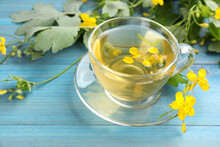 Glass Cup Of Aromatic Celandine Tea And Flowers On Light Blue Wooden Table, Closeup