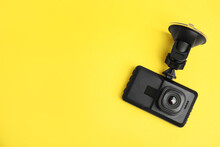 Modern Car Dashboard Camera With Suction Mount On Yellow Background, Top View. Space For Text