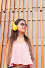 Pretty Girl Listening To Music With Her Headphones In The Street