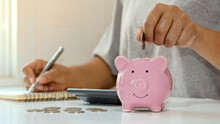 Women Put Silver Coins Into Piglets To Save Money And Save Money For Future Investment. Financial Concept.