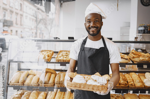 Canvastavla African American baker holding tray of bread in bakery