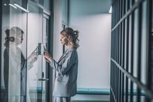 Woman Holding Smartphone To Reader On Door