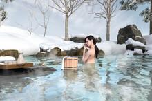日本酒を飲む黒髪の女性が露天風呂に入り野鳥と目が合う