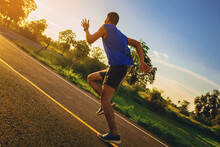 Silhouette Of Young Man Running Sprinting On Road. Fit Runner Fitness Runner During Outdoor Workout With Sunset Background. Selected Focus