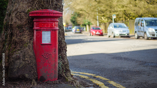 Canvas Print Photo of a 120-year old traditional British post box being swallowed up by a tre
