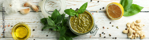 Canvas Print Pesto sauce and ingredients for cooking on wooden background