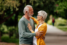 Senior Husband, Showing Affection To His Wife, Outside.