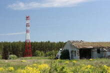 Collapsing Building And Telecommunications Tower Against The Background Of Forest And Blue Sky