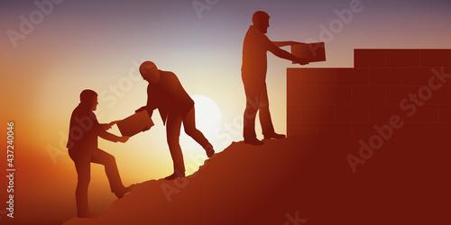 Obraz na plátně Symbole du travail d'équipe en entreprise avec un groupe qui s'entraide pour atteindre son objectif en bâtissant un mur au sommet d'une montagne