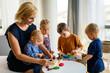 Leinwandbild Motiv Kids playing with plasticine. Teacher or mother play with children. People, kid creativity concept