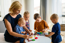 Kids Playing With Plasticine. Teacher Or Mother Play With Children. People, Kid Creativity Concept