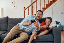 Happy Young Father And Son Playing Video Games While Spending Time At Home