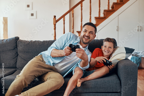 Fotografía Happy young father and son playing video games while spending time at home
