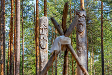 Siberia. A Pagan Temple In The Taiga With Two Wooden Idols. The Image Of Pagan Gods Is Carved On Wooden Logs.