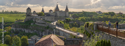 Fényképezés Backlit view of Kamianets-Podilskyi Castle, where tourists take selfies in the foreground with the castle itself in the background, Ukraine