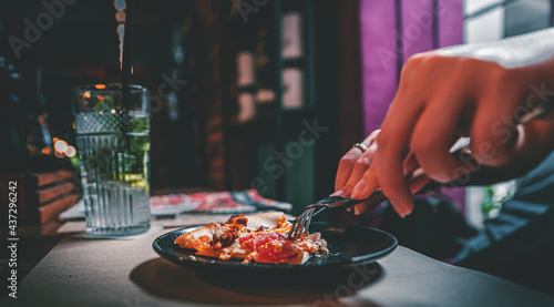 Fotografie, Obraz woman hands with knife and fork cutting pizza on table in cafe