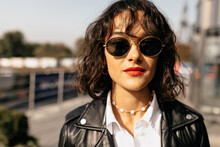 Bright Curly Woman With Red Lips In Sunglasses In Black Jacket And White Blouse Looking At Camera . Fashionable Girl In Good Mood Smiling Outdoor