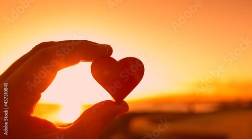 Fotografia, Obraz Hand holding red heart on sunset sky.