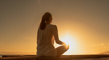 Young Woman Meditating By The Sea At Sunset. Being In A Calm State Of Mind Concept.
