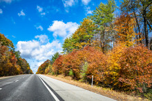 Landscape With A Skyline Abutting Highway With Picturesque Autumn Maple Trees On The Sides In New Hampshire New England