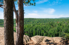 The View From A Rocky Lookout Point Spans Across A Massive Forest.