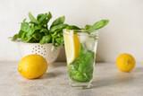 Glass of lemonade with basil on light background