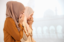 Two Young Asian Muslim Women In Hijab Dress Sitting Together And Praying With A Rosary In Hands. The Idea For Religious Ritual, Education, And Calm Of Mind