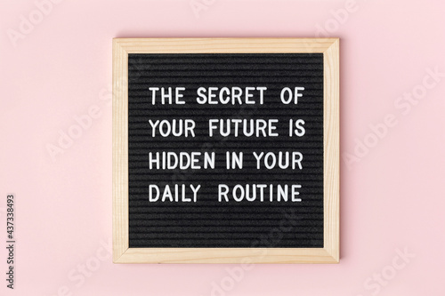 The secret of your future is hidden in your daily routine. Motivational quote on black letter board on pink background. Concept inspirational quote of the day. Greeting card, postcard