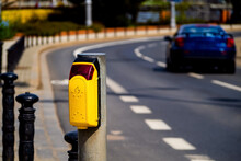 Pedestrian Crossing Button With Blurred Car On A Road