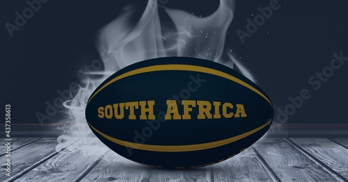 Compostion of rugby ball with text south africa on black background with white blur