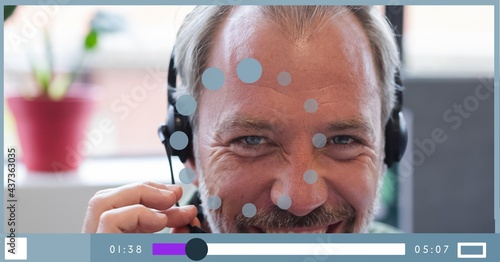 Composition of businessman talking on headset on video playback interface screen
