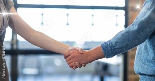 Composition of businessman and businesswoman shaking hands over cafe