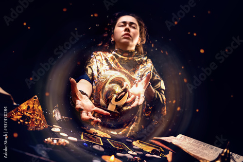Photo Portrait of a tense witch conjuring a magic energy ball with her hands