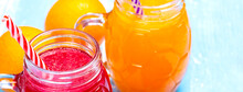 Orange And Strawberry Juice On Blue Wooden Table
