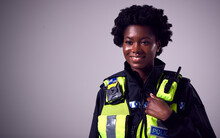 Studio Portrait Of Smiling Young Female Police Officer Against Plain Background