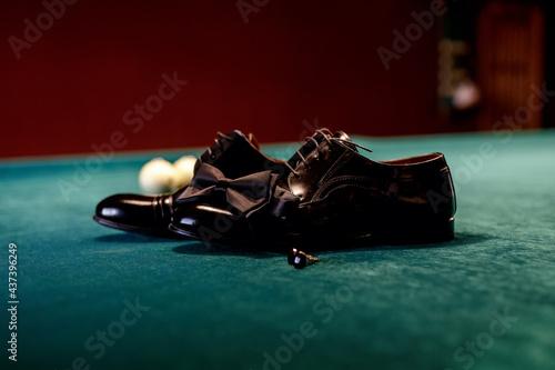 Obraz na plátně Black shoes and a groom's bow tie on a billiard table against a background of gr