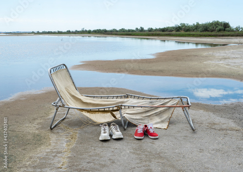 Obraz na plátně An old, vintage cot by the lake and a pair of sneakers