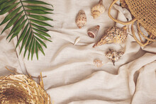 Summer Background: Straw Hat, Bag With Sea Shells, Palm Leaf On Textile Linen Background