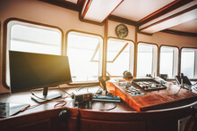 View Of A Cockpit Area Inside Of A Deckhouse Of A Modern Safari Or Cruise Yacht With A Control Panel On The Wooden Base And Many Navigation Devices: Compass, Radio Transceiver, Radars, And Dashboards