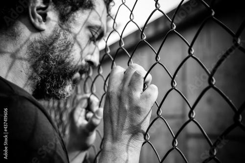 Foto Young man behind bars
