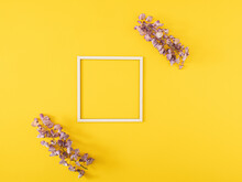 Two Fresh Purple Flowers With Cube Frame On Sunny Summer Illuminating Yellow Background With Copy Space. Minimal Natural Decorative Art. Minimal Flat Lay.