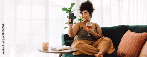 Fotografiet Woman having virtual happy hour with frineds using mobile phone