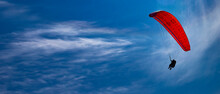 One Paraglider Flies On A Red Parachute In The Blue Sky. Paragliding On A Sunny Day.