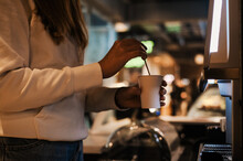 Young Woman Prepares Herself Coffee Through A Self-service Coffee Machine In A Cafe. Woman Near The Coffee Maker Makes Cappuccino