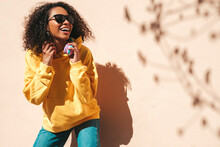 Beautiful Black Woman With Afro Curls Hairstyle.Smiling Hipster Model In Yellow Hoodie. Sexy Carefree Female Posing On The Street Background Near Wall In Sunglasses. Cheerful And Happy
