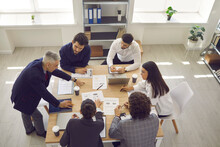 Brainstorming In A Modern Office. Serious Business Team Analyzes Sales Charts And Diagrams, Develops A New Strategy And Discusses Work Issues. Concept Of Teamwork On The Project. Top View.
