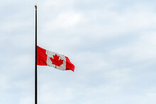 A Canadian Flag At Half Mast, Lowered In Remembrance Of The Indigenous Children Who Were Abused And Dies In Residential Schools. Overcast, Wide View.